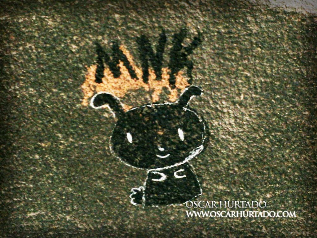 Black graffiti of a strange but cute creature over a dark textured wall