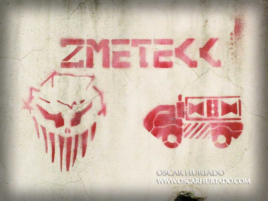 Red graffiti of an alienlike creature next to some bizarre vehicle