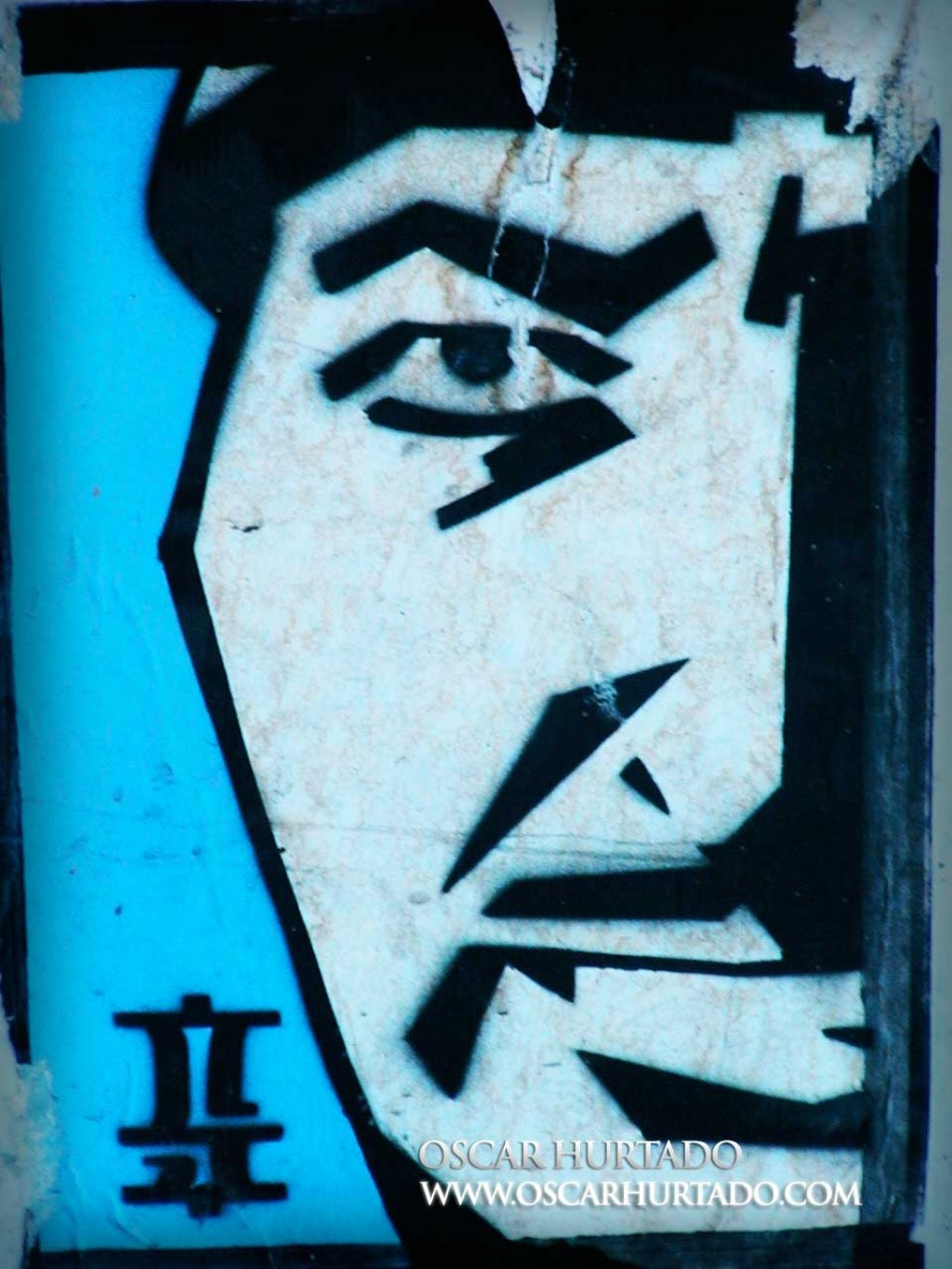 Iconic blue graffiti portraying the face of an Asian man