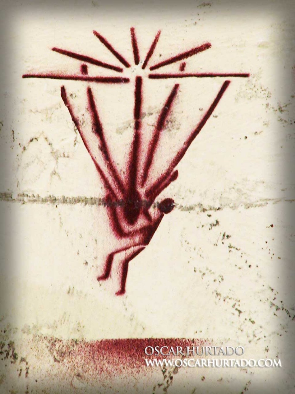 Red graffiti portraying a strange figure being abducted by aliens or attached to a kind of parachute