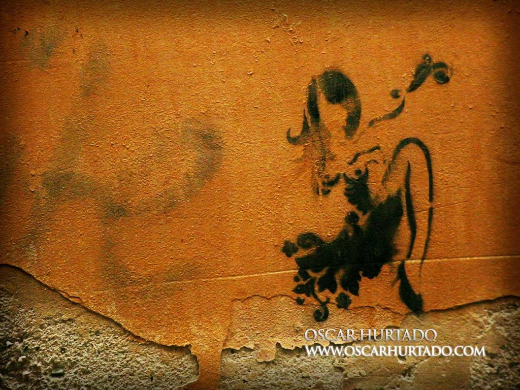 Black graffiti of a semi-nude woman in an erotic pose over an old orange wall surface