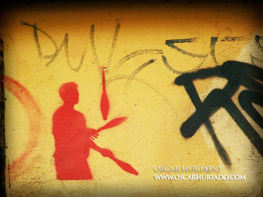 Red graffiti of a joggler against a dirty old orange wall surface