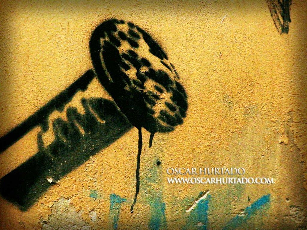 Bold black graffiti of a giant nailhead against an old orange wall surface
