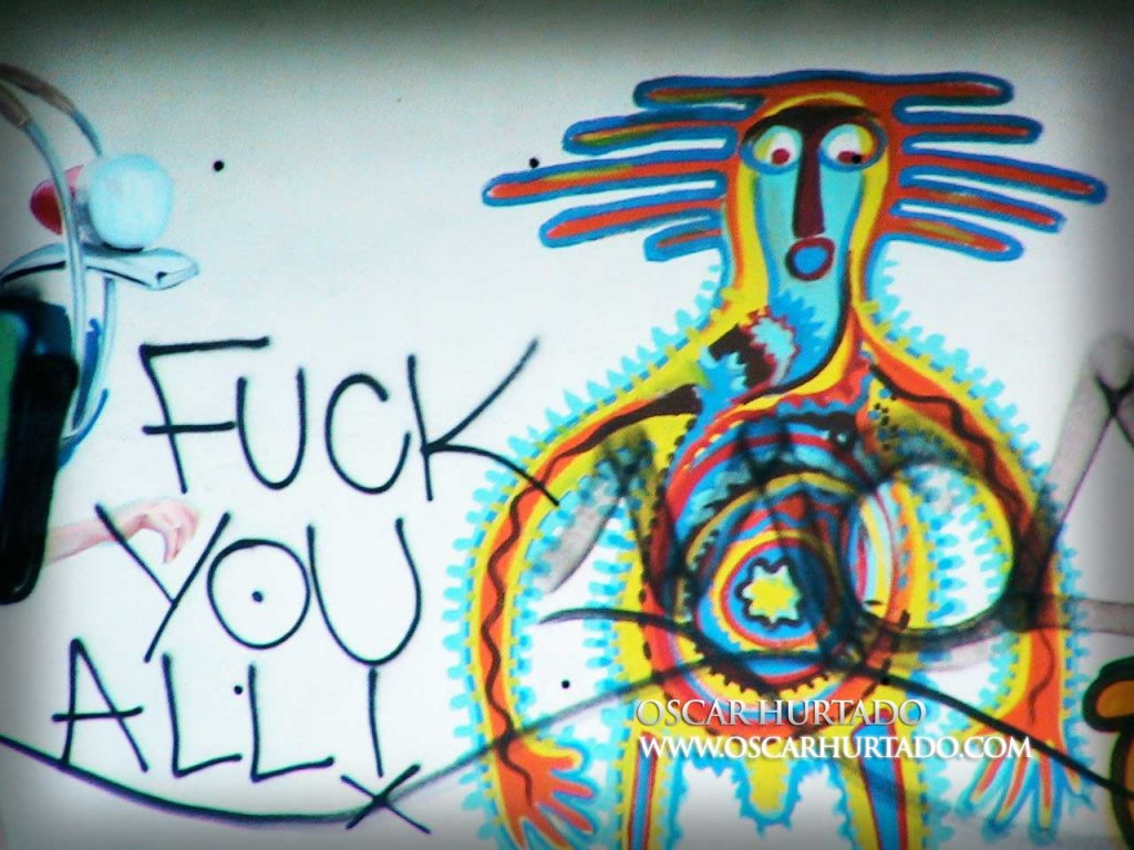 Colorful graffiti portraying a bizarre character lying next to a friendly message
