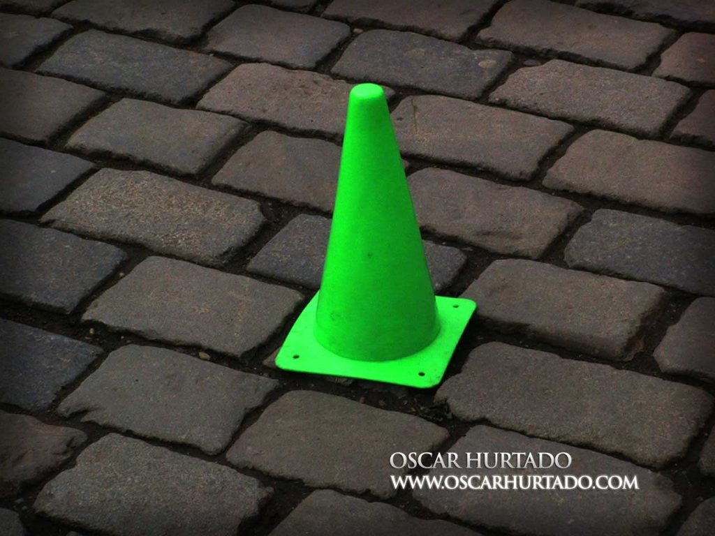 Shot of a bright neon green traffic cone found lying against the stone pavement
