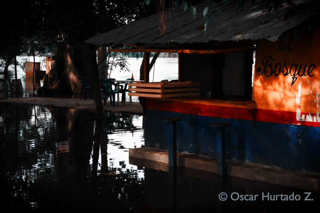 A deserted street bar is found almost floating over the flooded shores of Mompox