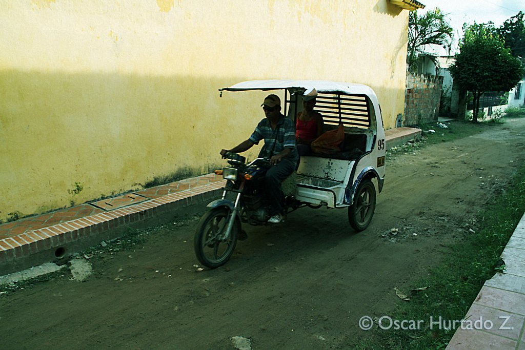 A woman goes for a ride on one of the typical three-wheel taxi bikes found in Mompox