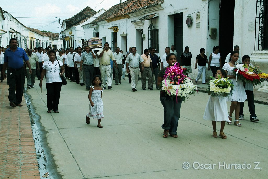 A woman and two girls carrying flowers, lead the way to the funeral of a local through the streets of Mompox