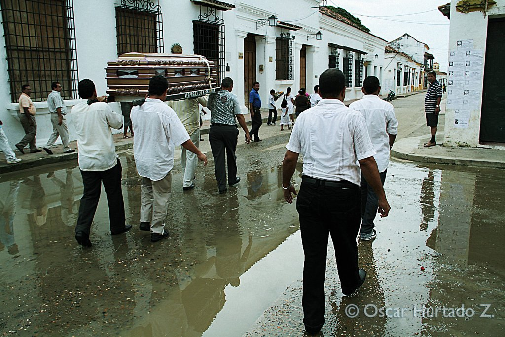 A group of men carry the coffin of a deceased local through the flooded streets of Mompox during one rainy afternoon