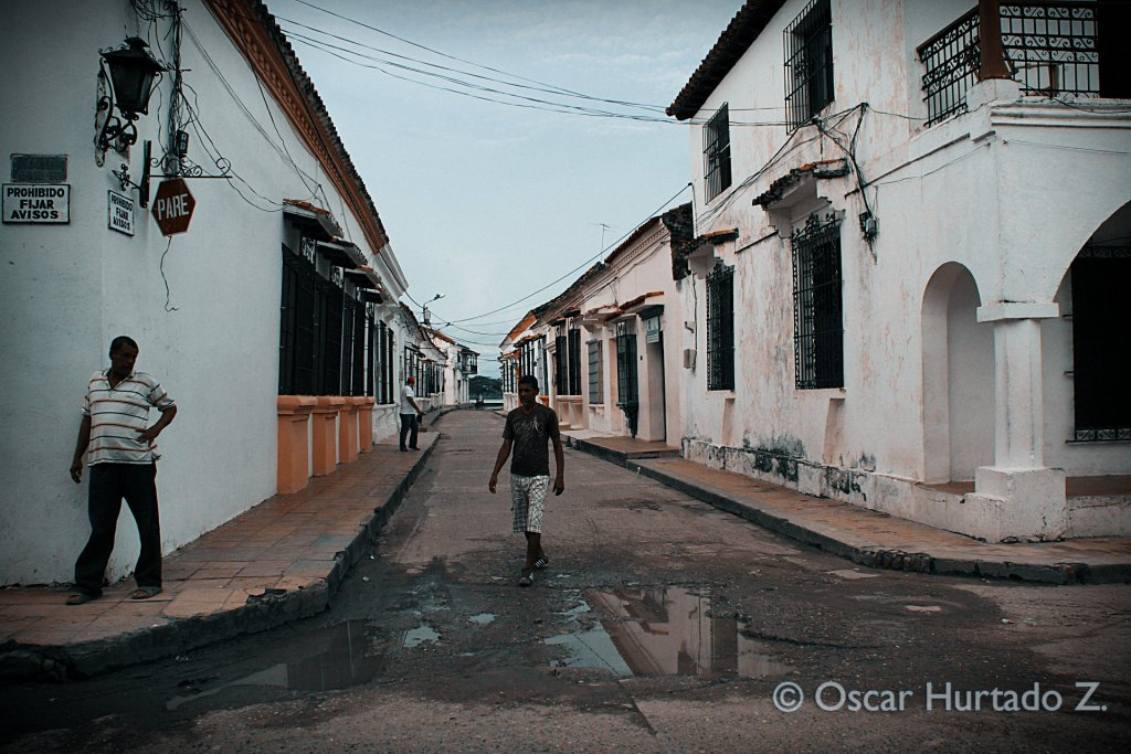 Locals wandering and walking around the colonial streets of Mompox during one rainy afternoon