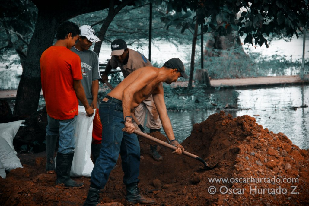 A group of local men work hard on filling up sandbags that will be used to prevent additional flooding of the streets in Mompox