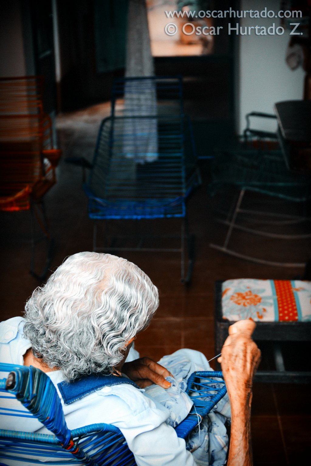 Picturesque view of an old lady peacefully sewing in her living room during one humid summer afternoon