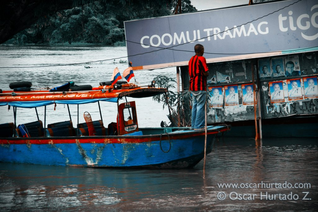 A man leads the way of his colorful boat across the flooded shores of the Magdalena river