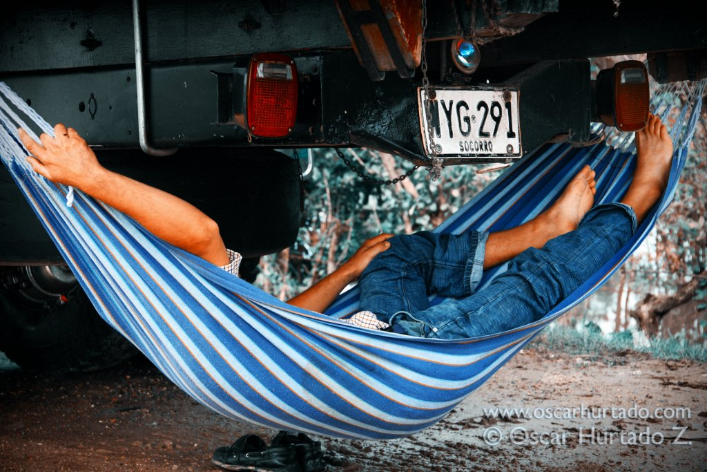A driver takes a nap on his hammock hanging on the back of his truck while awaiting for permission to transit across the Madgalena River via a ferry